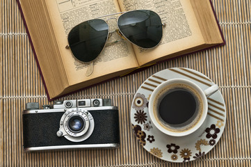 Retro camera,cup of a coffee, book and sunglasses
