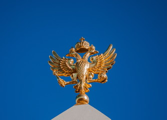 Golden two-headed eagle on a background of blue sky
