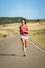 Female athlete running in country road