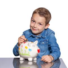 Kind wirft Euro Münze in ein buntes Sparschwein
