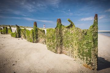 Damaged Larssen sheet pile wall on beach. Lighthouse on back.