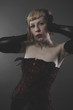 Love, sensual blond in red corset on gray background