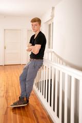 Teenager lehnt an Treppengeländer in Altbauwohnung
