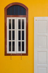 A vintage door and window on yellow wall