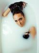 beauty young brunette girl in bath, taking milk spa