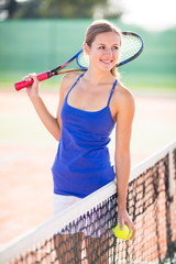 Portrait of a pretty, young tennis player  on  a court