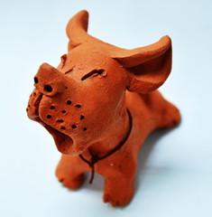 Red clay dog barking