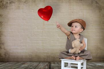 Kleines Mädchen zeigt auf einen Herzballon
