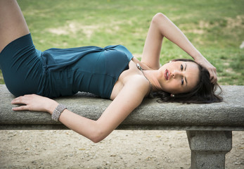 Attractive elegant young woman on stone bench