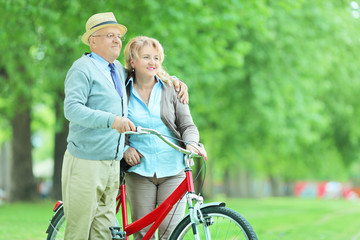 Mature couple pushing a bicycle in park