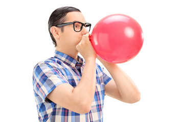 Young man blowing up a balloon