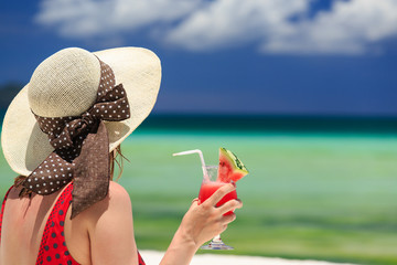 woman with watermelon cocktail on the beach