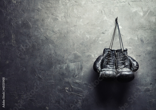old boxing gloves hang on nail on texture wall - 65131900