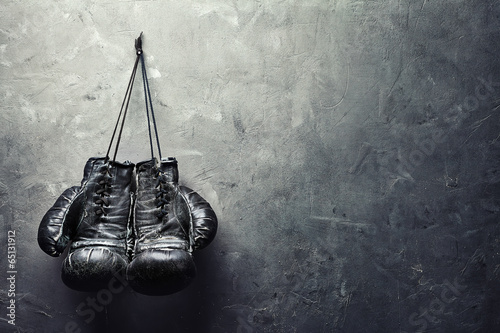 old boxing gloves hang on nail on texture wall - 65131912