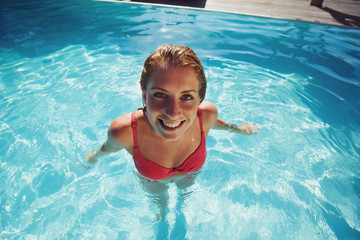Pretty young woman relaxing in a swimming pool