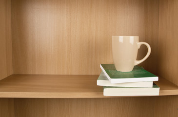 Books and cup on a shelf