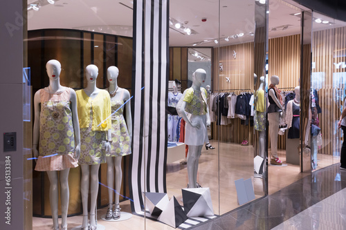 Boutique display window with mannequins in fashionable dresses - 65133384