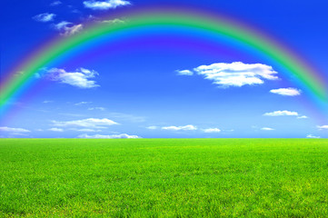 Green meadow, blue sky and a rainbow
