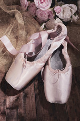 Ballet pointe shoes on dark  wooden background