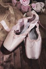 Ballet pointe shoes on dark  wooden background