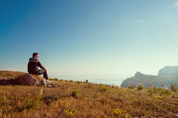 A young man sits on a hill and enjoys sunset