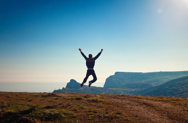 young man jumping off a cliff with his arms raised