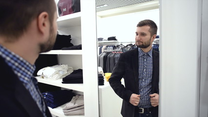 Young man chooses for himself new clothes at the mall. He tries