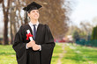 Proud college graduate holding diploma in park