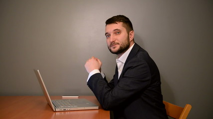 Young businessman sitting with  laptop on a gray background. Sid