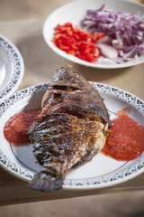 Baked tilapia served with red pepper sauce