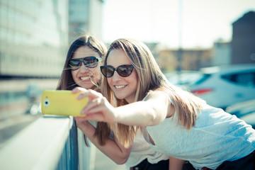 two beautiful young women using smart phone selfie