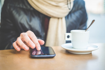 close up of woman hands with smartphone and cup of coffee