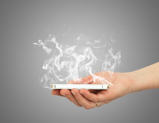 Hand holding smart phone with white smoke