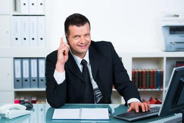angestellter sitzt am computer und telefoniert