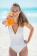 Closeup on young woman showing sun block creme
