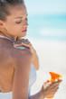 Young woman applying sun screen creme