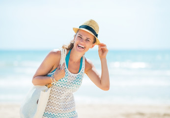 Happy young woman in hat on beach