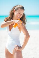 Happy young woman applying sun block creme