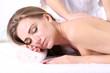 Beautiful young woman having back massage in spa salon