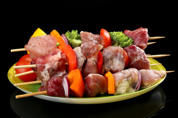 Raw pork kebab on black background