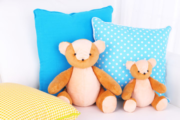 Two bears toy with pillows on sofa