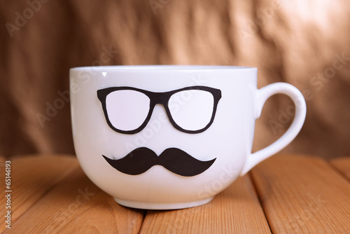 Cup with mustache on table on brown background