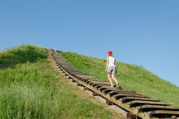 tourist woman climb strairs on mound hill