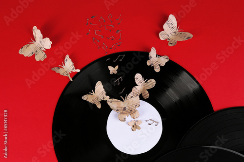 Old vinyl record with paper butterflies, on red background