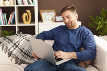 Handsome man with contemporary laptop at home