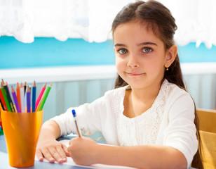 Cute hispanic girl writing at school