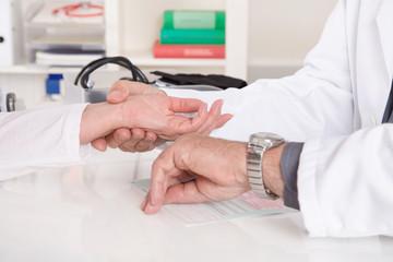 Arzt misst der Patientin den Puls am Handgelenk