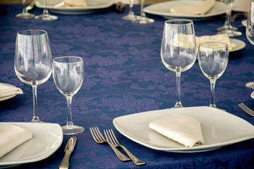 Setting table with dish, glasses and cuterly
