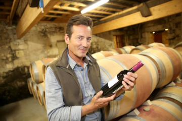 Handsome winegrower holding bottle of red wine