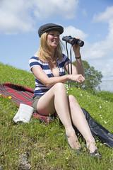 Woman sitting on grass holding binoculars